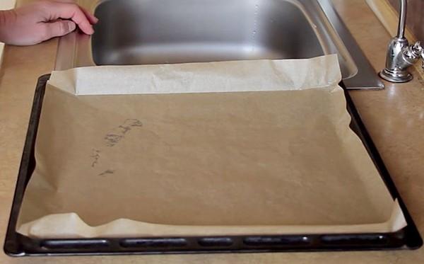 Застилаем противень пергаментом для запекания пирожных из заварного теста