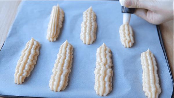 Мешком для кондитерских изделий наносим на пергамент будущие пирожные из заварного теста