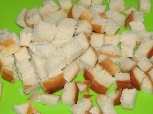 Нарезаем батон на маленькие кубики для приготовления пирожного из сухарей